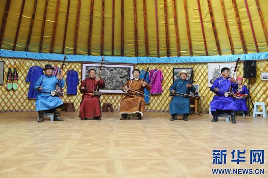 牧民艺人为游客演奏蒙古族四胡。新华网 曹桢摄