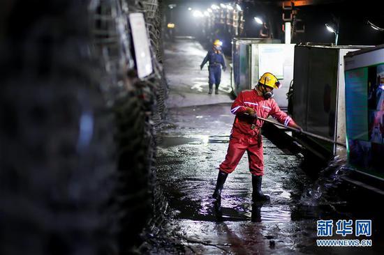 11月4日,在地下400米的采煤工作面,国源矿业公司的一名矿工在清理矿井环境。新华社发(马世超 摄)