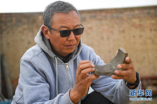 11月1日,考古人员对西汉中晚期疑似大型粮仓建筑基址中出土的瓦件进行研究。新华社记者 彭源 摄