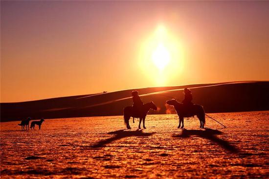 夕阳红色的余晖洒在草原的雪地上冰天雪地也暖意融融