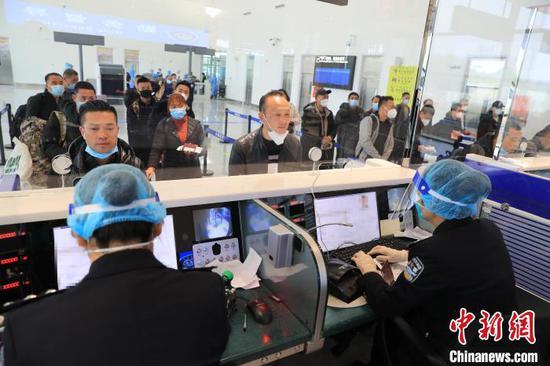 图为边检人员为乘客办理乘机手续。 塔娜 摄