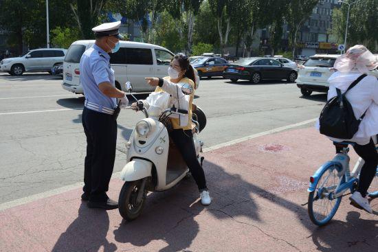 交警拦停不戴头盔的电动车驾驶员。