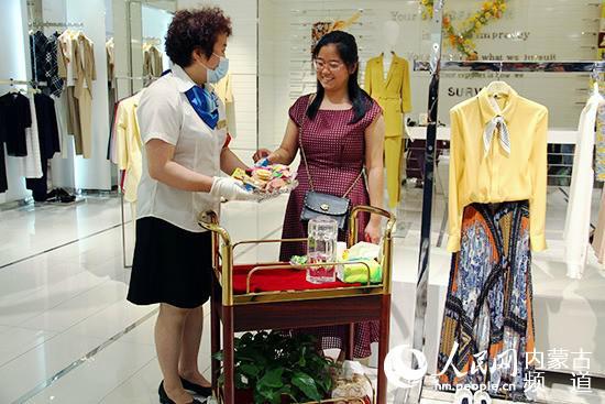 民族商场内,党员胡秀荣推着流动服务车为顾客提供服务。张聿修 摄