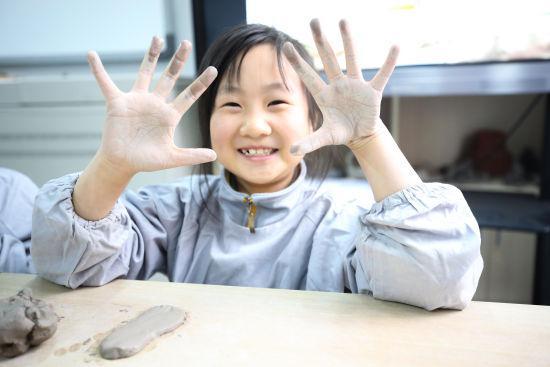图为同学们正在制作陶艺草鞋。