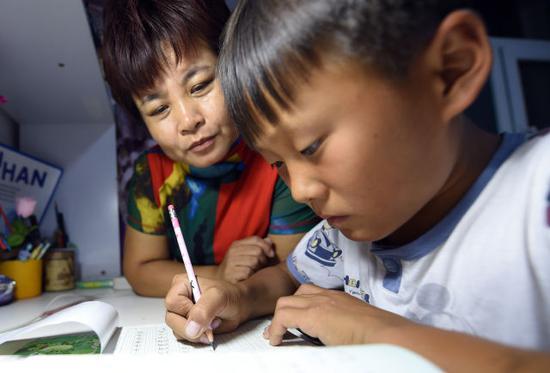 9月10日,李珺在辅导王辅正写作业。