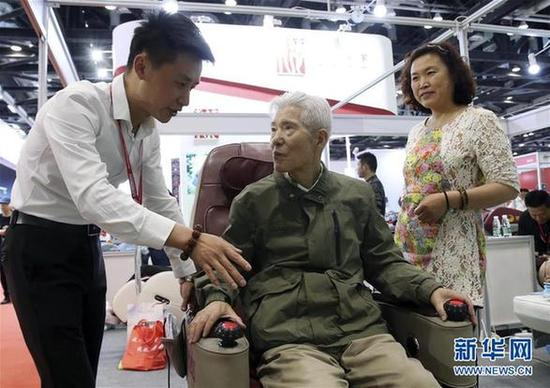 5月9日,一名老年人在博览会现场体验一款理疗设备。