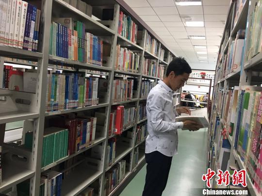 图为白灵光在图书馆看书。 张玮 摄