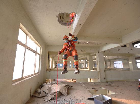 """图为救援人员打通楼板向下输送救援人员营救""""被困者""""。"""