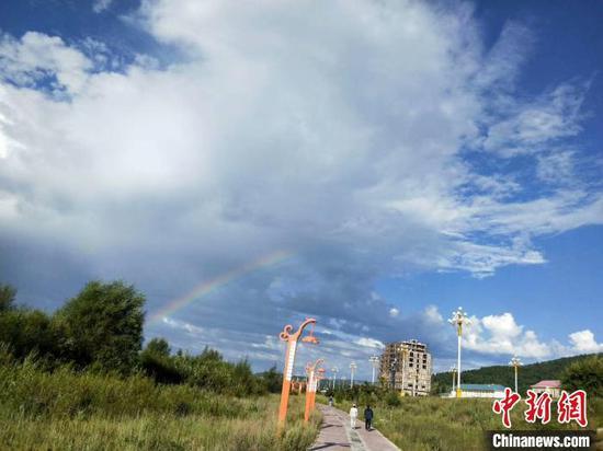 图为7月22日根河市区上空出现彩虹,晨练的群众穿上了厚厚的外套。 纪成成 摄