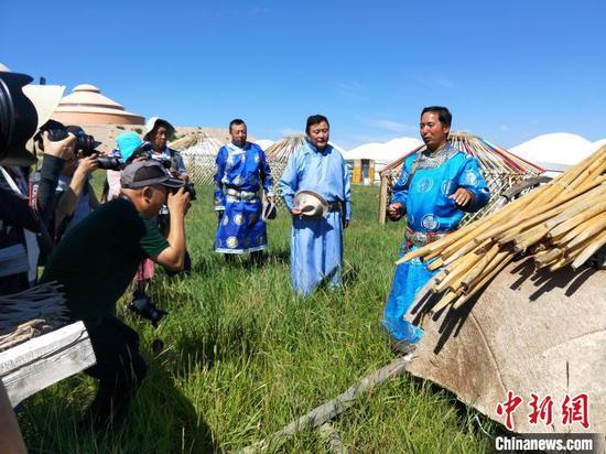 布仁巴雅尔向媒体记者讲解蒙古包制作技术。 邱春凤 摄