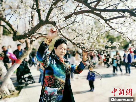 图为呼和浩特公主府公园游人如织,游客踏青赏花。 张玮 摄