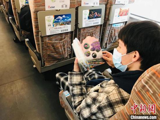图为旅客观看《鄂尔多斯四季赏花文旅活动》宣传册。 刘奇 摄
