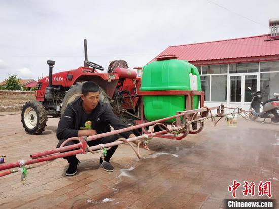 图为赵洪民在调试玉米打药机。 胡建华 摄