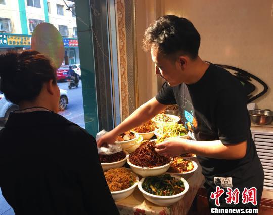图为张龙为客人挑选咸菜。 张玮 摄