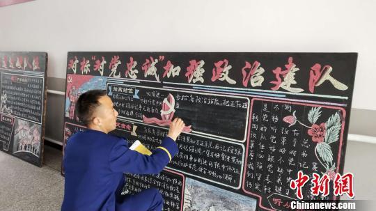 图为彝族小伙布依小兵书写板报。 张林虎 摄