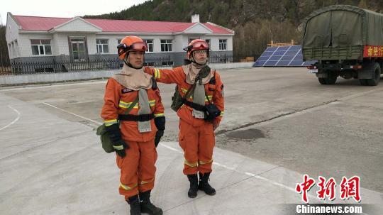 图为布约小兵(左)展示打火时的随身装备。 张林虎 摄