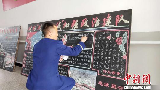 图为布约小兵在书写板报。 张林虎 摄