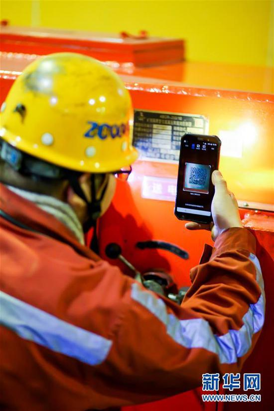 11月4日,在地下400米的采煤工作面,国源矿业公司的一名矿工在使用手机软件读取采煤机械的运行参数。新华社发(马世超 摄)