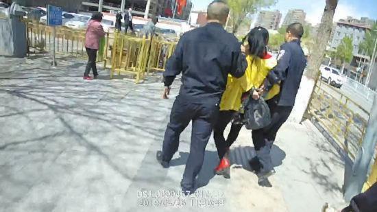 图为涉事女子被警察带离。
