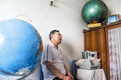 68岁的包广田与两个手绘地球仪。