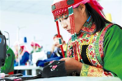 """一名身着民族服饰的""""绣娘""""正在专注地刺绣。"""