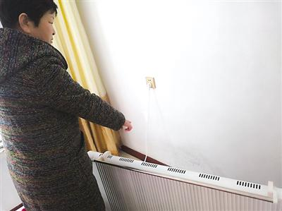 周女士用电暖气烘干墙壁