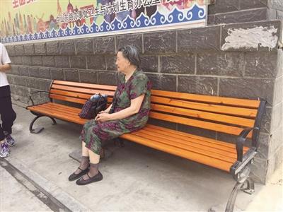 一位老人在团结巷1号院门口处安放的长椅上休息
