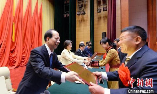 图为内蒙古自治区党委书记、人大常委会主任石泰峰为全区脱贫攻坚先进集体代表颁发奖牌。 袁永红 摄