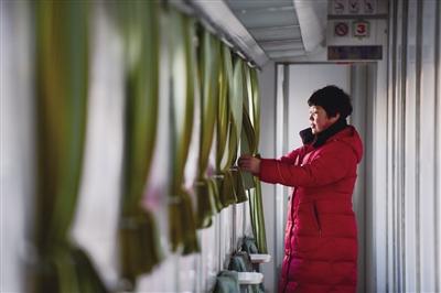 在从集宁南发往通辽的6041次列车上,乘务员周龙艳在整理卧铺车厢窗帘(1月24日摄)