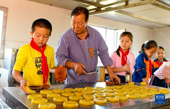9月8日,在伊金霍洛旗蘇布爾嘎嘎查,非遺傳承人巴圖青克爾(左二)為學生傳授空殼餅制作技藝。