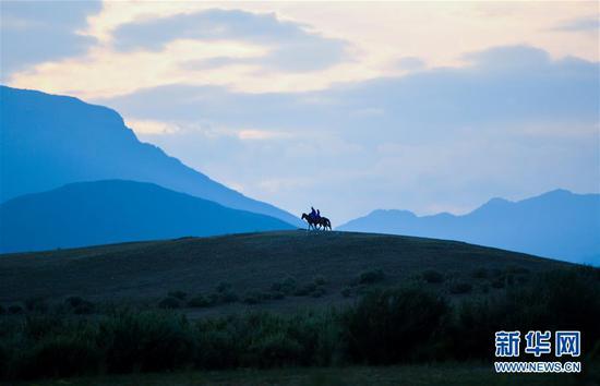 """呼日查毕力格和女儿在山丘上骑马(7月20日摄)。 今年35岁的呼日查毕力格是内蒙古赤峰市巴林左旗查干哈达苏木的牧民。从小喜欢蒙古马的他经过20年的努力,使自家的马群不断壮大,从最初的1匹发展到如今的100多匹。现阶段呼日查毕力格把主要精力放在了培养优秀的蒙古赛马上,这样既可以有较高的收入,又能够让蒙古马得到更多人的认可。 2018年3月,呼日查毕力格在自己的家乡查干哈达苏木创建了""""黑骏马旅游度假营""""。在他的度假营中,游客可以亲身参与到挤马奶、骑马、打马印、剪马鬃等丰富多彩的马文化体验项目中,深入了解蒙古马独特的生活习性和特点。 新华社记者 彭源 摄"""