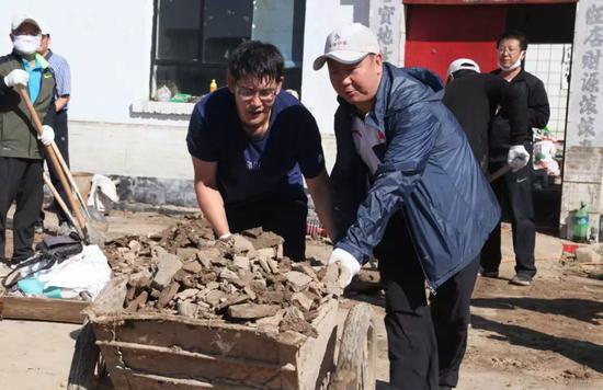 史万钧帮助受灾村民收拾院落。