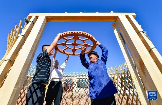 9月8日,在伊金霍洛旗蘇布爾嘎嘎查,非遺傳承人圖孟吉日嘎(右)為游客介紹蒙古包營造技藝。