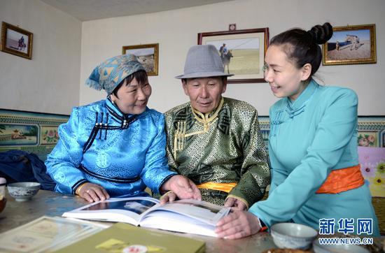 图为牧民巴拉图苏和与家人欣赏摄影作品。