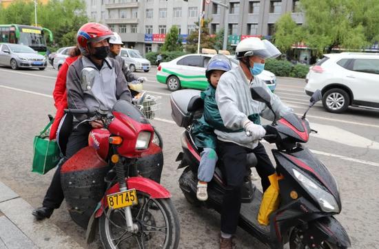 马路上多数电动车车主佩戴头盔
