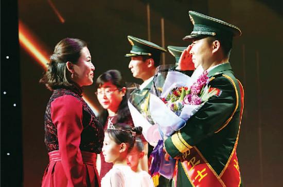 """官兵家属代表为""""北疆亮丽边防卫士""""颁奖。"""