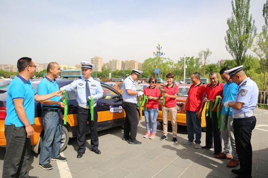 民警为爱心送考驾驶人发放绿丝带。摄影 韩斌