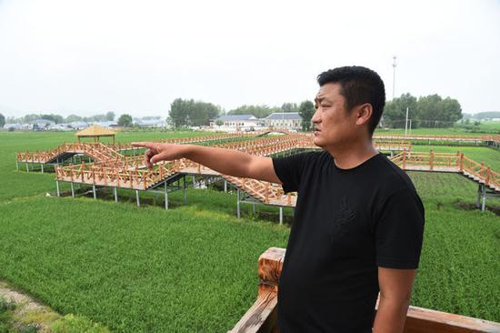"""三合村党支部书记许忠峰介绍着三合村的""""特色致富经""""。"""
