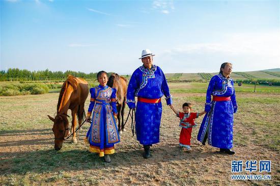 """呼日查毕力格(左二)与家人牵马走在草场上(7月20日摄)。 今年35岁的呼日查毕力格是内蒙古赤峰市巴林左旗查干哈达苏木的牧民。从小喜欢蒙古马的他经过20年的努力,使自家的马群不断壮大,从最初的1匹发展到如今的100多匹。现阶段呼日查毕力格把主要精力放在了培养优秀的蒙古赛马上,这样既可以有较高的收入,又能够让蒙古马得到更多人的认可。 2018年3月,呼日查毕力格在自己的家乡查干哈达苏木创建了""""黑骏马旅游度假营""""。在他的度假营中,游客可以亲身参与到挤马奶、骑马、打马印、剪马鬃等丰富多彩的马文化体验项目中,深入了解蒙古马独特的生活习性和特点。 新华社记者 彭源 摄"""