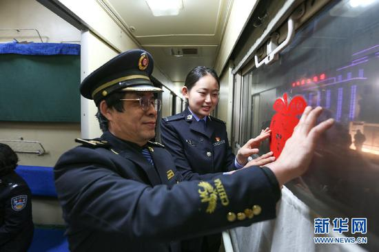 边检民警和列车员一起装饰列车。新华网发(朱宇奇摄)