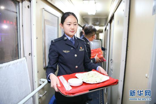 边检民警为归国旅客送上热腾腾的饺子。新华网发(郭鹏杰摄)