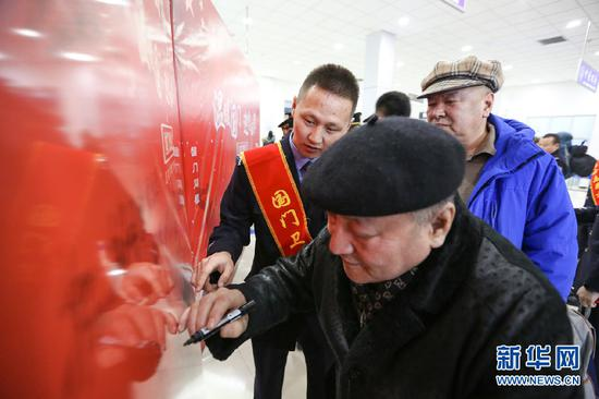 归国返乡旅客在国门留言板上签名。新华网发(朱宇奇摄)