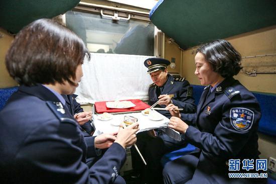 边检民警和列车长孙国祥(右二)一起在列车上吃饺子。新华网发(郭鹏杰摄)
