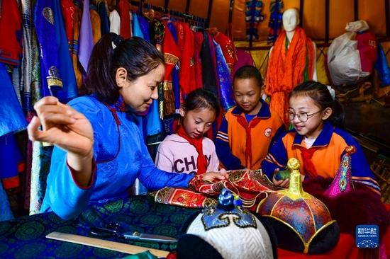 9月8日,在伊金霍洛旗蘇布爾嘎嘎查,非遺傳承人娜拉(左一)為學生講解蒙古族服飾制作技藝。
