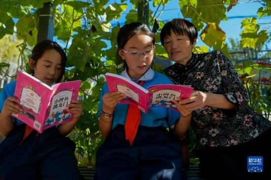9月8日,在喀喇沁旗南臺子小學,呂瑞蓮在校園里與學生一起讀書。新華社記者 李志鵬 攝