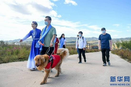 9月11日,工作人员引导一名视障人士前往开幕式现场。