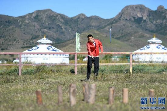 9月11日,一名视障人士在内蒙古自治区盲人那达慕活动上体验打布鲁。