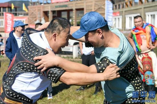 9月11日,视障人士在内蒙古自治区盲人那达慕活动上体验蒙古式摔跤。