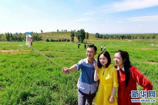 9月14日,游客在位于伊金霍洛旗纳林陶亥镇的内蒙古蒙泰集团满来梁煤矿采煤沉陷区景区里拍照留影。新华网 发(王正 摄)