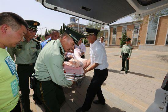 官兵将患病旅客抬上救护车。